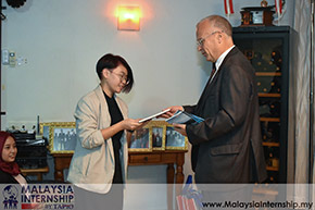 student receives a book from the Ambassador