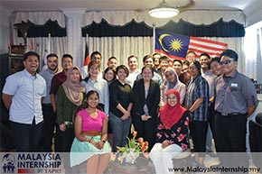 Student from multi-diverse culture taking a group photo with a Malaysian flag at the back