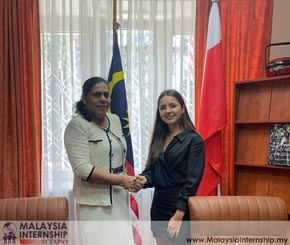 Two ladies handshake in front of the Malaysia flag