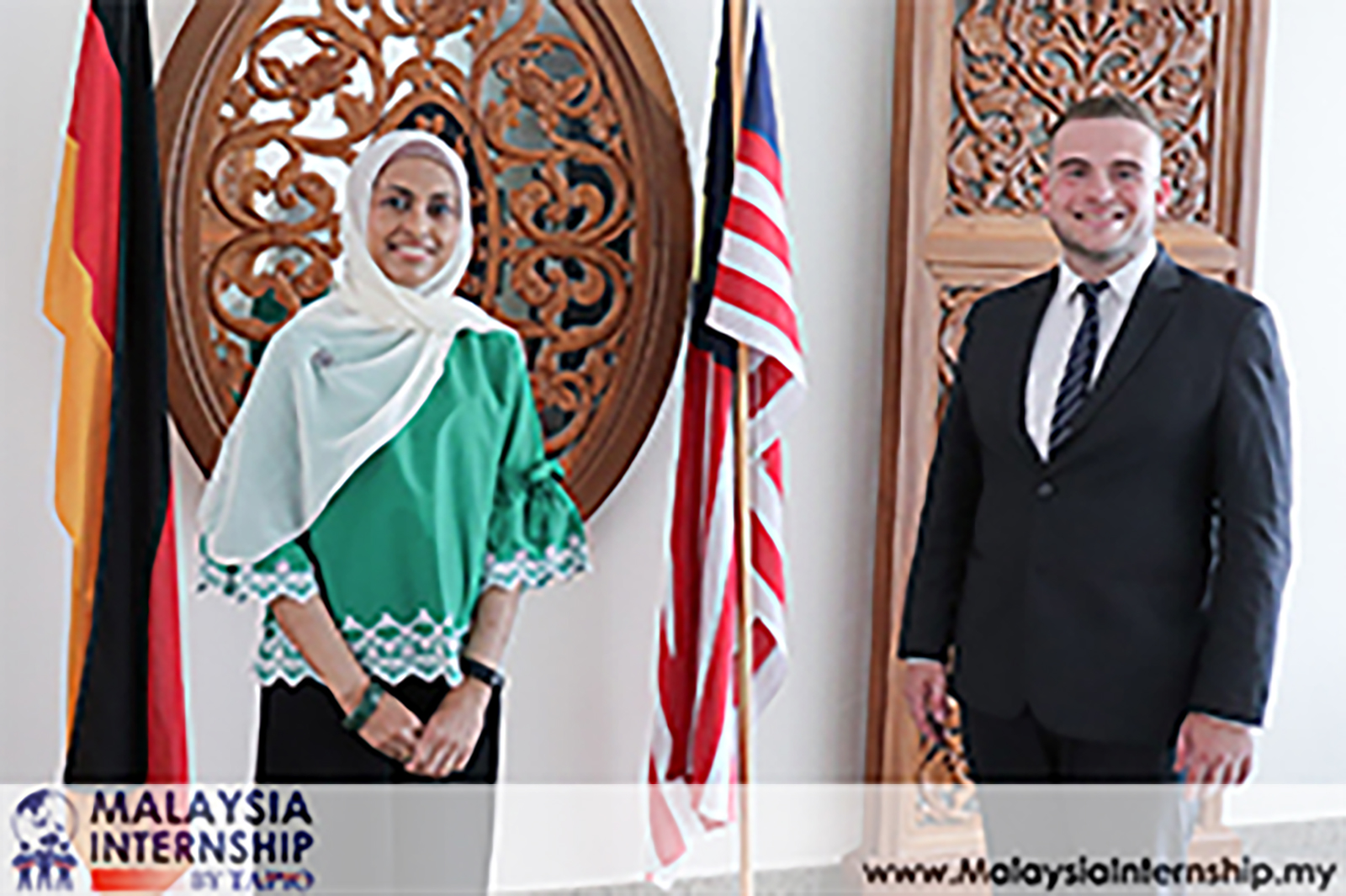 two people standing in front of Malaysia and Germany flags